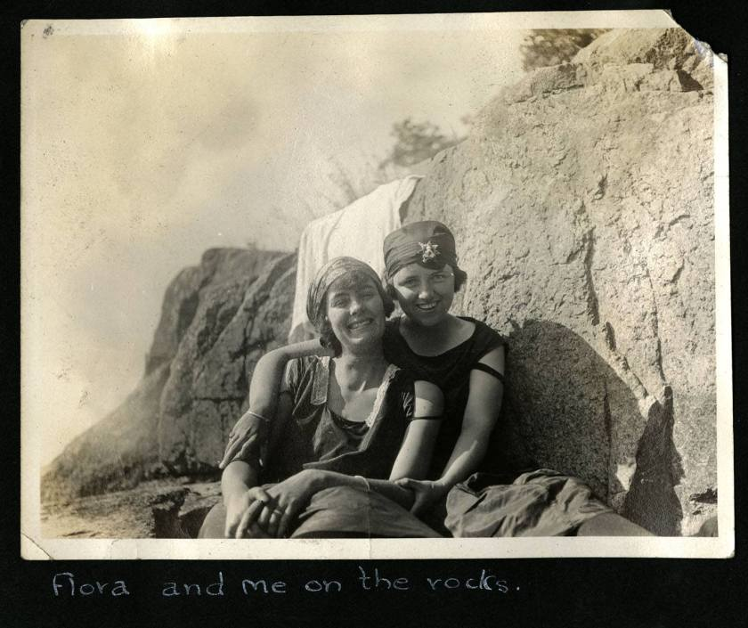 Two ladies sitting together on rocks, one with her arm around the other..