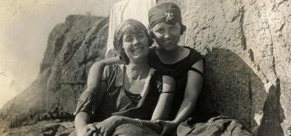 Two ladies sitting together on rocks, one with her arm around the other.