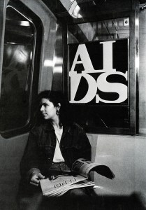 """Black and white photo reproduction of a young woman sitting in a subway car. The AIDS poster, """"General Idea 'AIDS'"""" hangs directly behind her"""