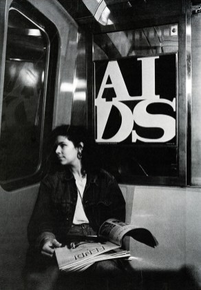 "Black and white photo reproduction of a young woman sitting in a subway car. The AIDS poster, ""General Idea 'AIDS'"" hangs directly behind her"