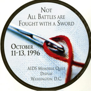 Round sticker advertising the AIDS Memorial Quilt display on the National Mall in Washington, D.C. In the center of the sticker is a picture of a sewing needle that is threaded with a red thread curved into the shape of an AIDS ribbon