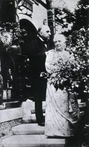 A middle aged white man in a suit standing outdoors on steps with a woman in a dress..