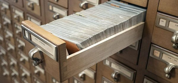 A drawer of cards pulled out in a card catalog.