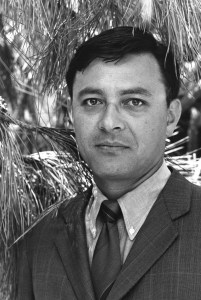 A black and white photograph of a man in a suit outdoors.