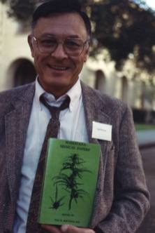 A man in a suit poses outdoors holding up a book.