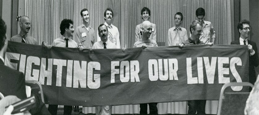 "White men stand holding a banner that says ""fighting for our lives"""