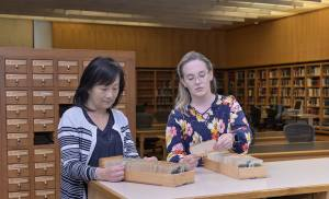 Two women look at cards in drawers removed from the card catalog.
