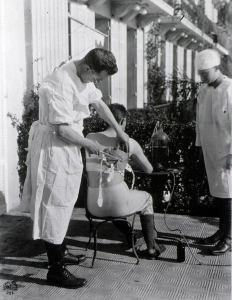 A man in a white gown uses an instrument on a male patient's back.