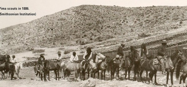 A black and white photograph of men on horses in an arid landscape reprinted in a pamphlet.