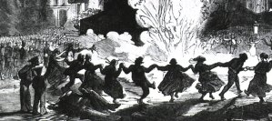 An engraving of a large crowd of people watching others dance in a ring around a bonfire.