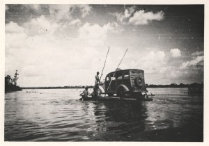 An early model automobile on a raft on a river.
