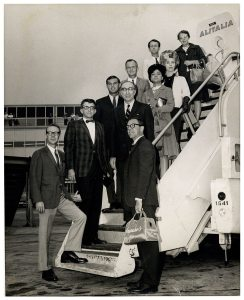 Ten people standon the stairs to an airplaine.