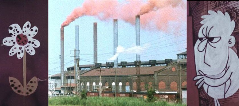 Brown smoke comes out of tall pipes from an industrial area behind a brick building in a grassy landscape.