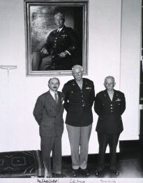 Three white men stand under a painted portrait hung on a wall.