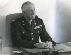 An older white man in a military uniform seated at a desk.