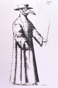 Person wearing a hat, a mask suggestive of a bird beak, goggles or glasses, and a long gown.