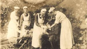 Nurses and patients ourdoors wearing gas masks.