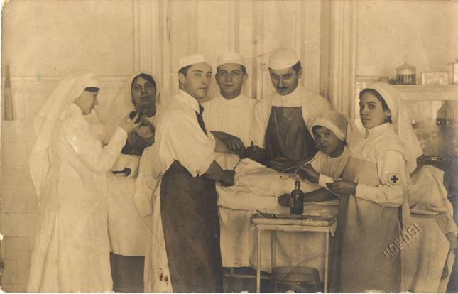 A postcard with a photograph of an operating room, people wear aprons and caps but not masks.