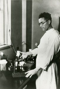 A man in an apron works with test tubes and syringes.
