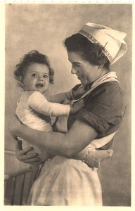 Postcard featuring a black and white photograph of a nurse in a cap and apron holding a young child.