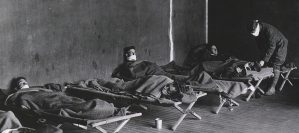 Men wearing white cloth masks lay on wooden cots under wool blankets.