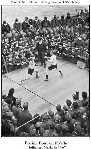 Two men in shorts and gloves box on the deck of a ship watched by a dense crowd most of whom wear cloth masks.
