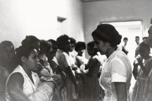 Dr. Helen Rodriguez-Trias, a Latina female, facing a crowd of mothers.