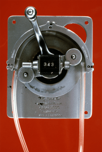 A photograph of a mechanical device with DeBakey's name and patent number stamped on it.