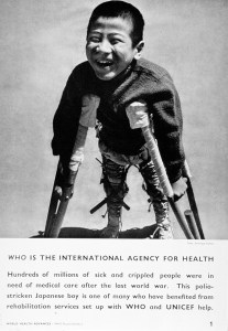 Young, smiling boy walking with crutches