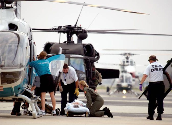 People in uniform help a person on a stretcher surrounded by parked helicopters.