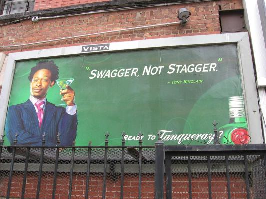 A billboard featuring a Black man in a suit holding a martini glass.