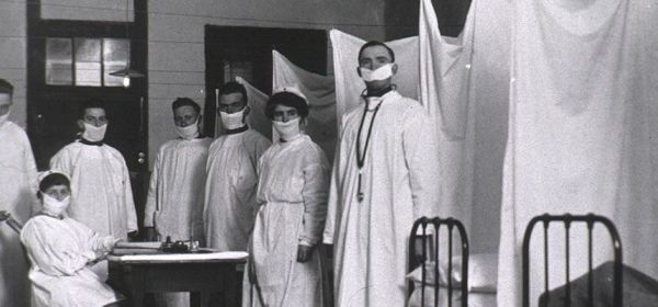 Seven staff male and female in white smocks and masks pose in a room with beds separated by sheets.