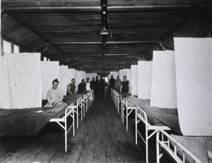In a long wood floored room lined with beds separated by sheets people pose sitting at the foot of the beds.