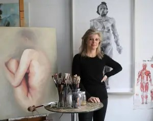 A white woman poses between two artworks featuring human figures by a table with paintbrushes.