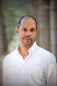 An informal portrait of a black man outdoors.
