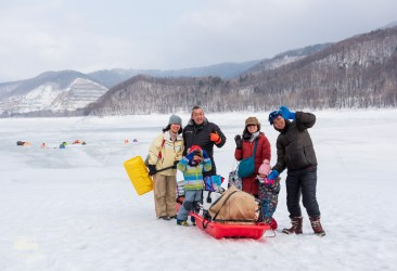 A family approaces a fun day of ice fishing and eating. In Hokkaido the winter is just another season full of its own outdoor activities!