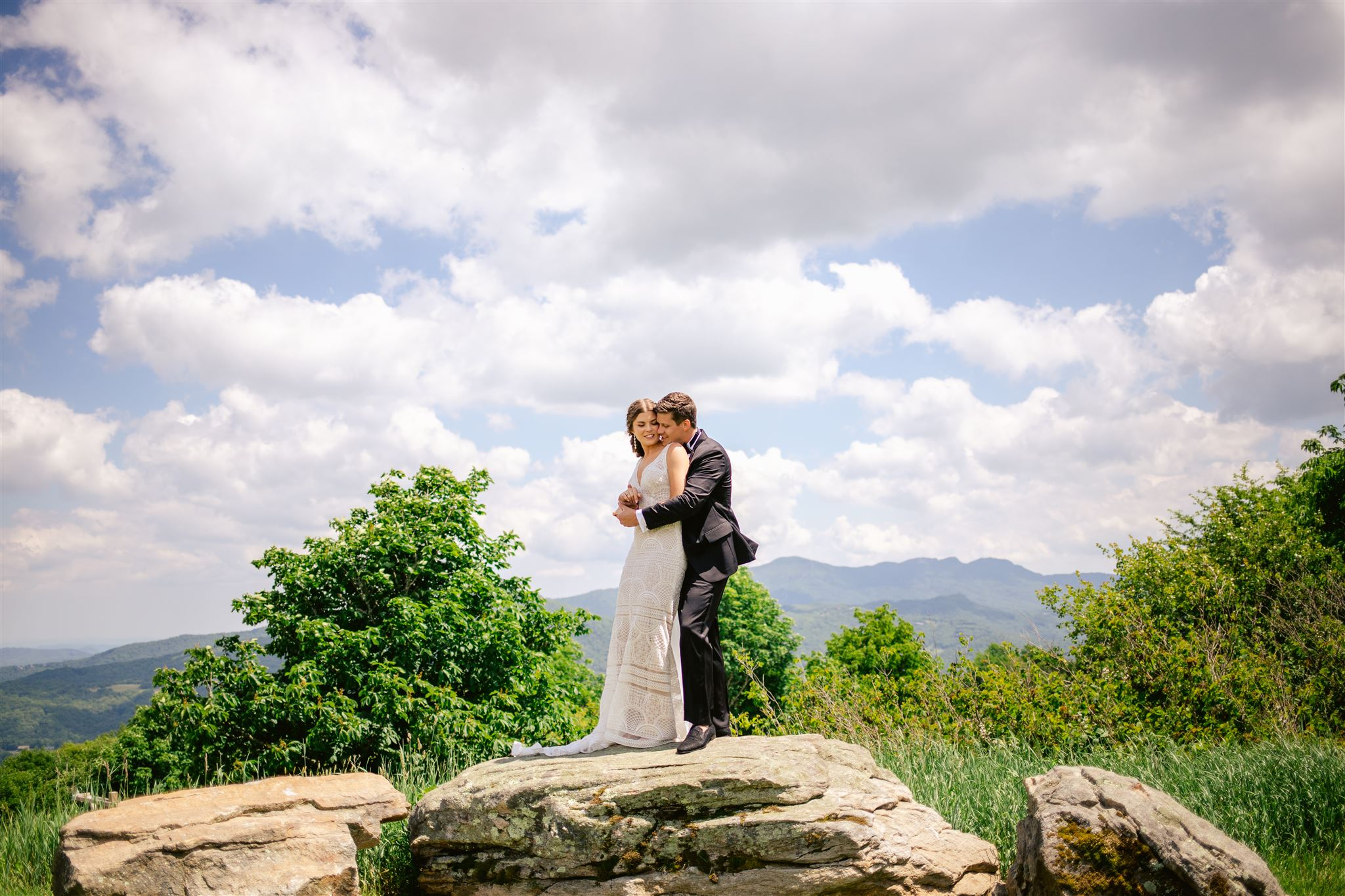 Bride and groom hugging with the blue ridge parkway in the background