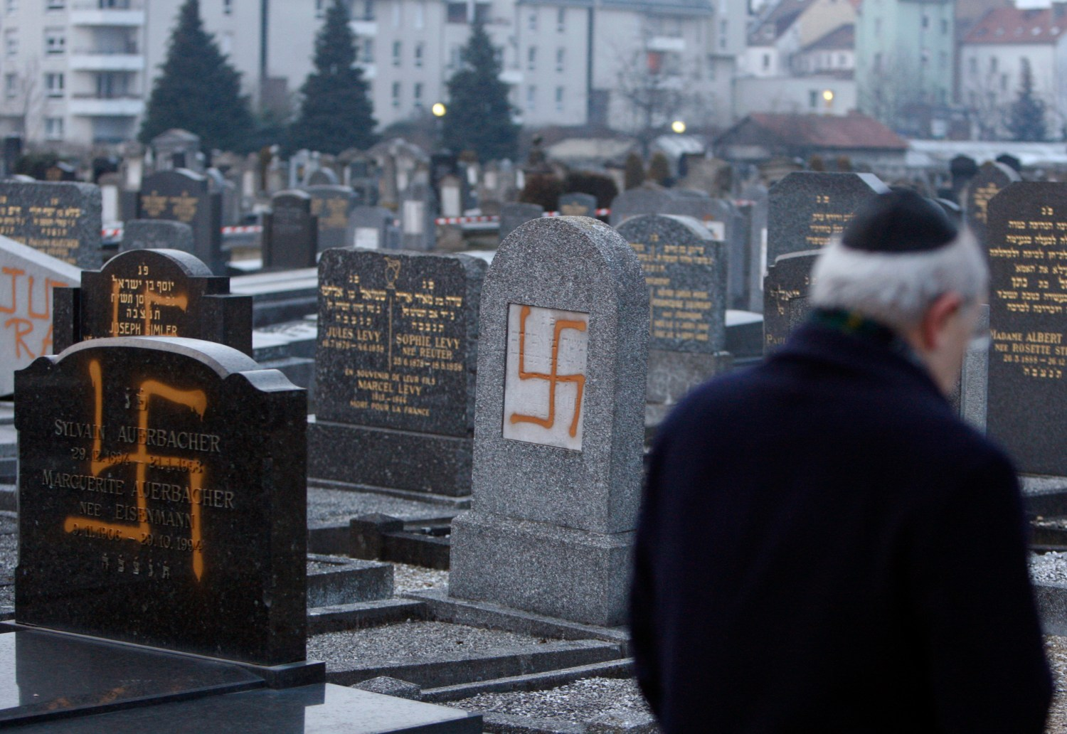 Francis Levy, head of the North Alsacian Jewish community, inspects tombstones desecrated by vandals with Nazi swastikas in the Jewish Cemetery of Cronenbourg near Strasbourg, January 27, 2010. REUTERS/Vincent Kessler (FRANCE - Tags: RELIGION CRIME LAW) - RTR29JAP
