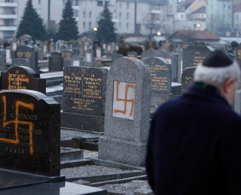 Francis Levy, head of the North Alsacian Jewish community, inspects tombstones desecrated by vandals with Nazi swastikas in the Jewish Cemetery of Cronenbourg near Strasbourg, January 27, 2010. REUTERS/Vincent Kessler (FRANCE