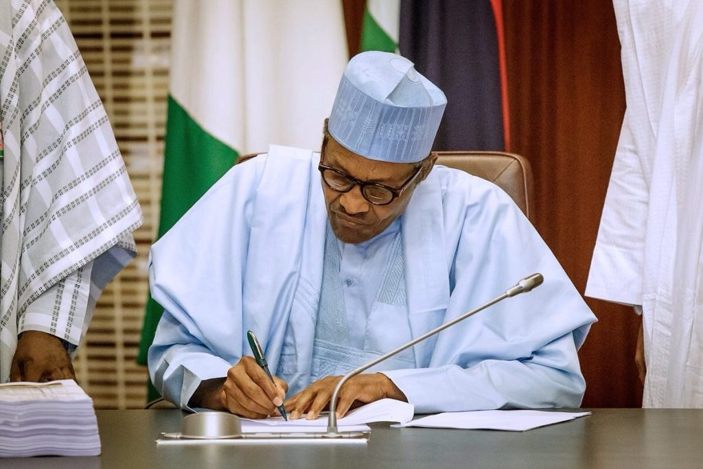 a bespectacled man on traditional African attire and a hat, signing a document