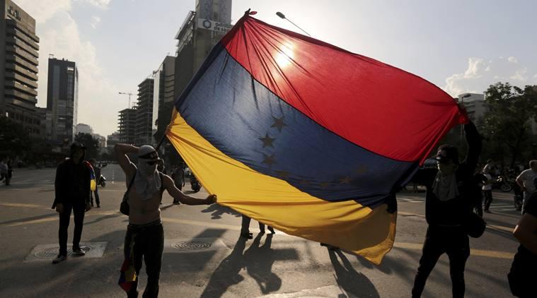 Demonstrators hold a Venezuelan flag upside down