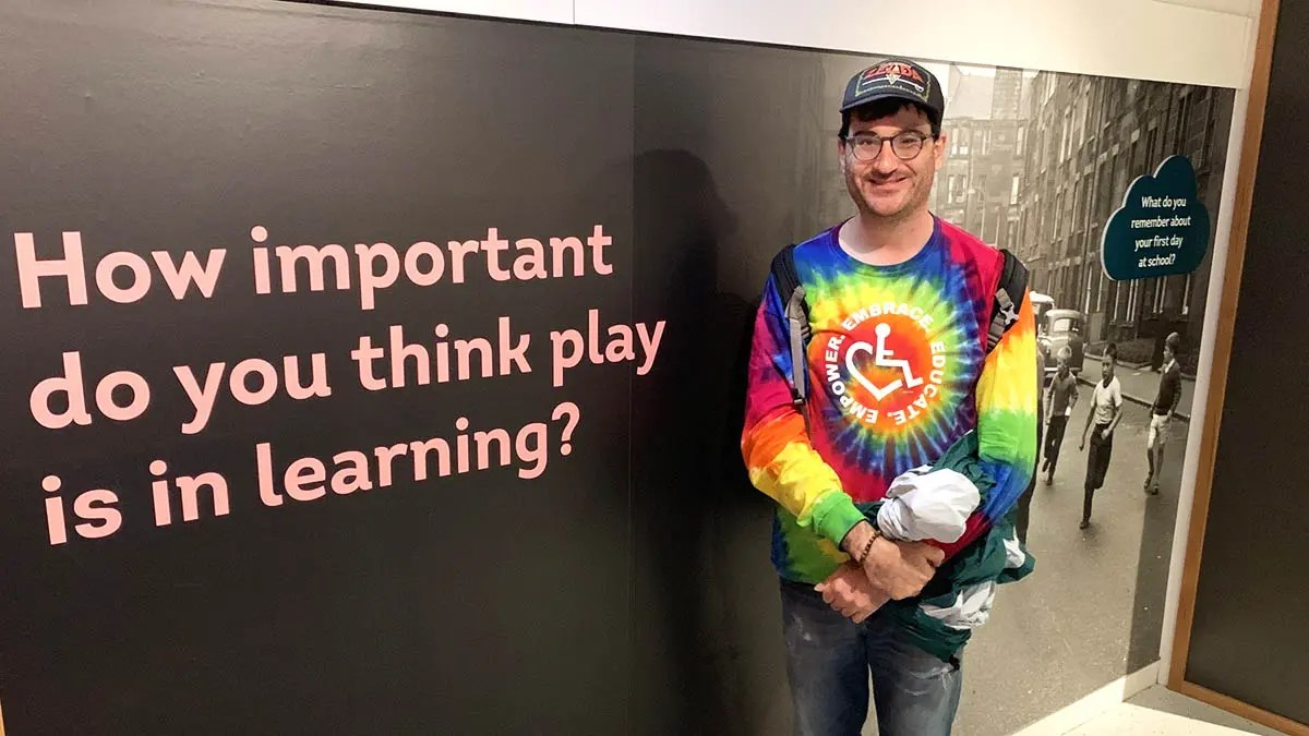 "Jason Ross, white man in glasses and facial hair in tie-dye shirt with disability symbol next to a blackboard with words ""How Important do you think play is in learning"""