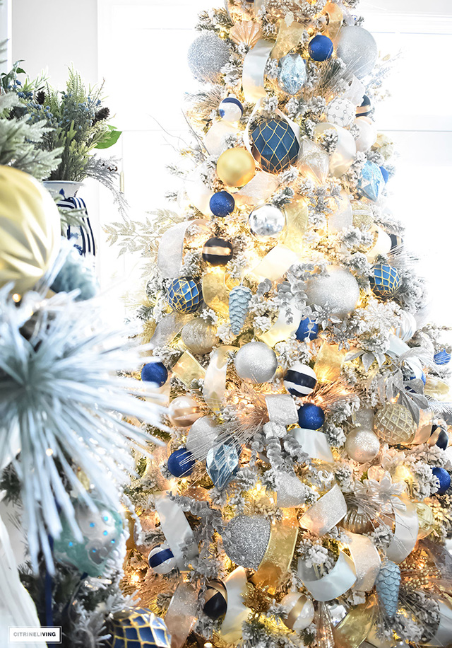 white christmas tree with blue and gold decorations. Black Bedroom Furniture Sets. Home Design Ideas