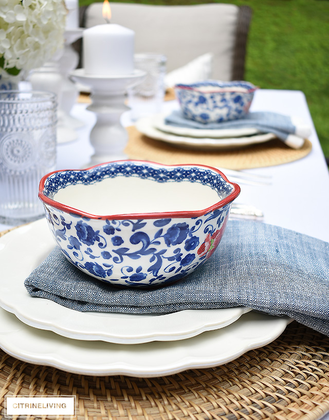 Vintage inspired outdoor late summer tablescape with white scalloped dishes and blue and white bowls.
