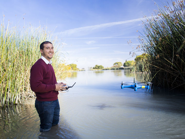 A man in red sweater and jeans stands in a marsh holding a UAV control. A quadrocopter is hovering over the water next to him.
