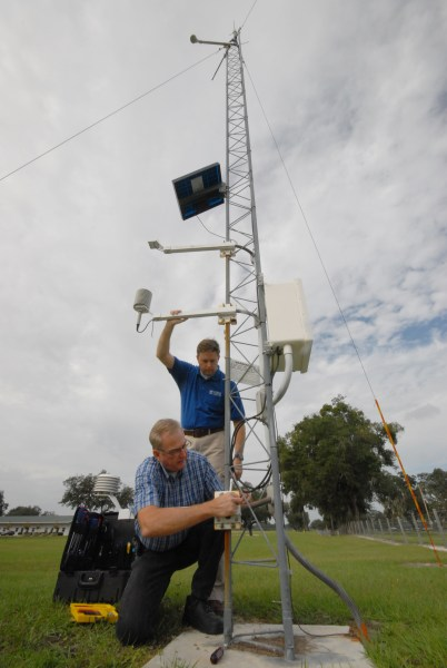 Rick Lusher, standing, and George Braun, field site supervisor for FAWN, install a temperature sensor at a monitoring station located at UF's Plant Science Research and Education Unit in Citra, Fla.  Spring 2008 Impact Magazine image.  UF/IFAS File Photo.