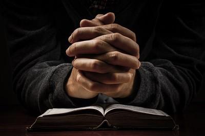 Praying man hand and bible on desk.