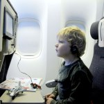 child in airplane seat watching screen