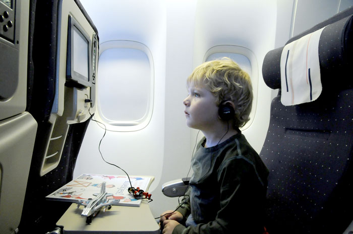 child flying in airplane seat watching screen