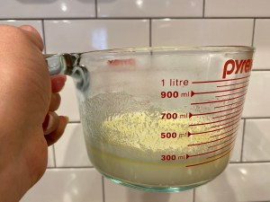 Picture of sugar, butter, water, milk in a measuring cup- Quick Cinnamon Rolls- city foodie farm